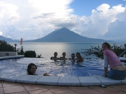 University students relax in a hot tube and watch a volcano during a service learning trip to Guatemala.
