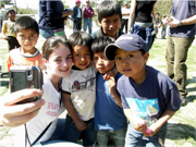 High school girl takes a selfie with children at a small rural school in Guatemala.