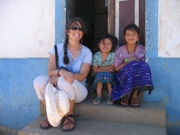 Woman with rural children sitting in front of a house during a Guatemala with a Purpose trip.