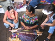Two women from the US receiving a weaving lesson during a Guatemala with a Purpose trip.